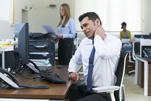 Man at desk with sore neck
